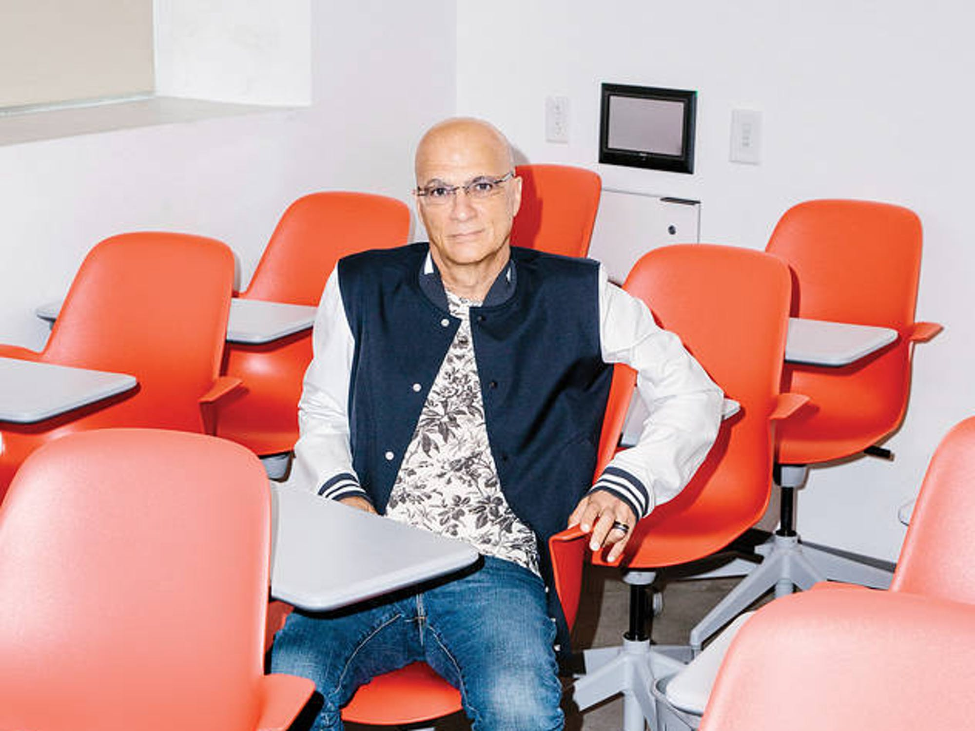 Jimmy Iovine sits on stylized red furniture
