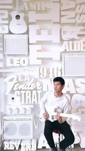 A young man sits on a stool holding a white guitar. Behind him is word art on a wall, also all in white