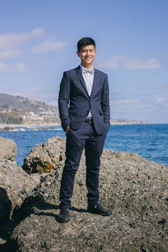 A young man stands on a rocky beach in a suit