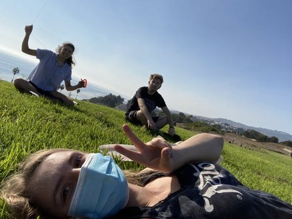Three students sitting or laying on grass