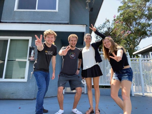 Four students hand gesturing peace sign
