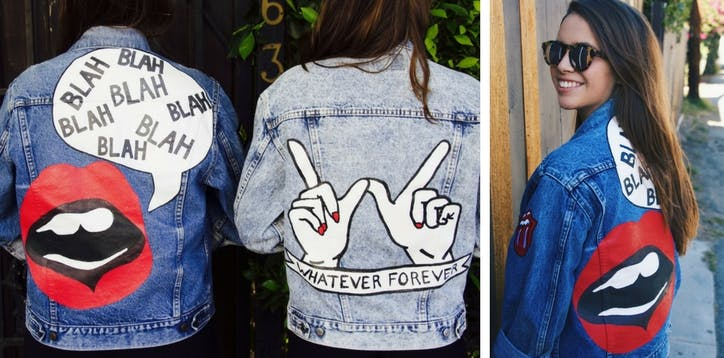 """A young woman shows off two denim jackets. One has lips painted on it and a speech bubble with """"Blah blah blah."""" The other has two hands in a W shape and says """"Whatever Forever"""""""
