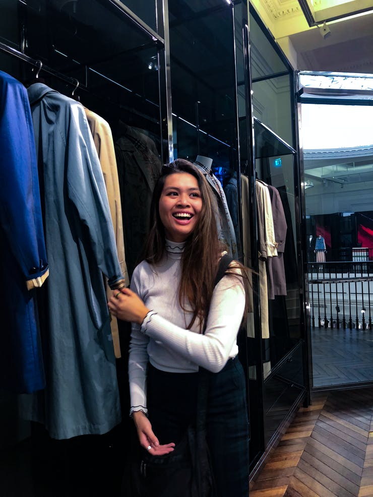 A young woman grins while standing in a closet