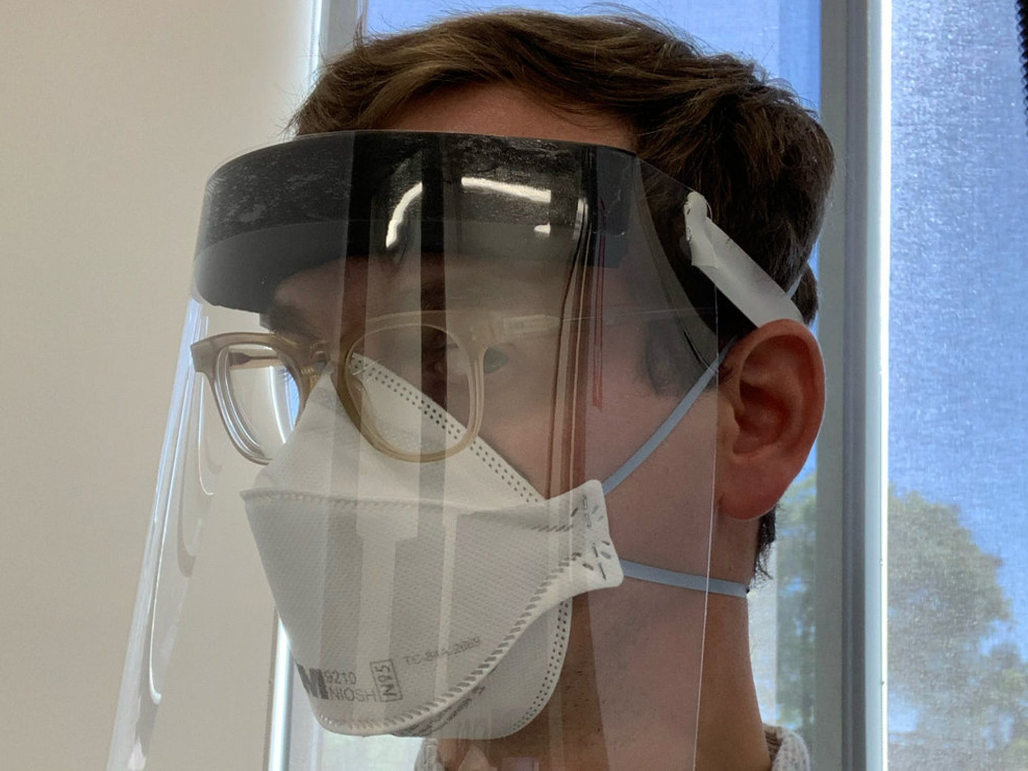 Male wearing face shield, mask, and glasses