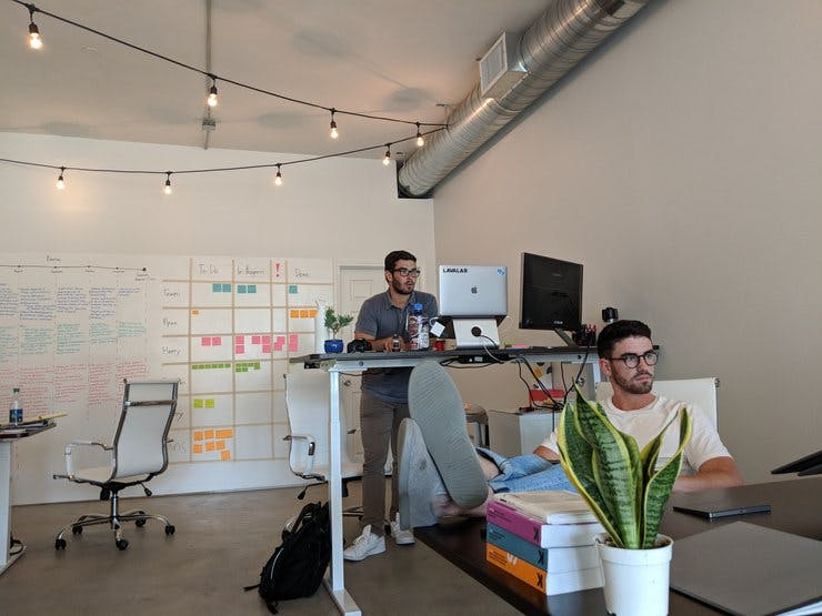 Young men sit at desks in a startup environment