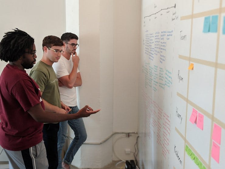 Three young men contemplate a board of post-it notes