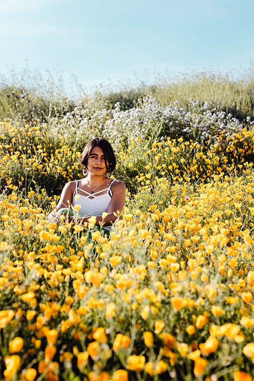 A young woman stands amidst a meadow of yellow flowers