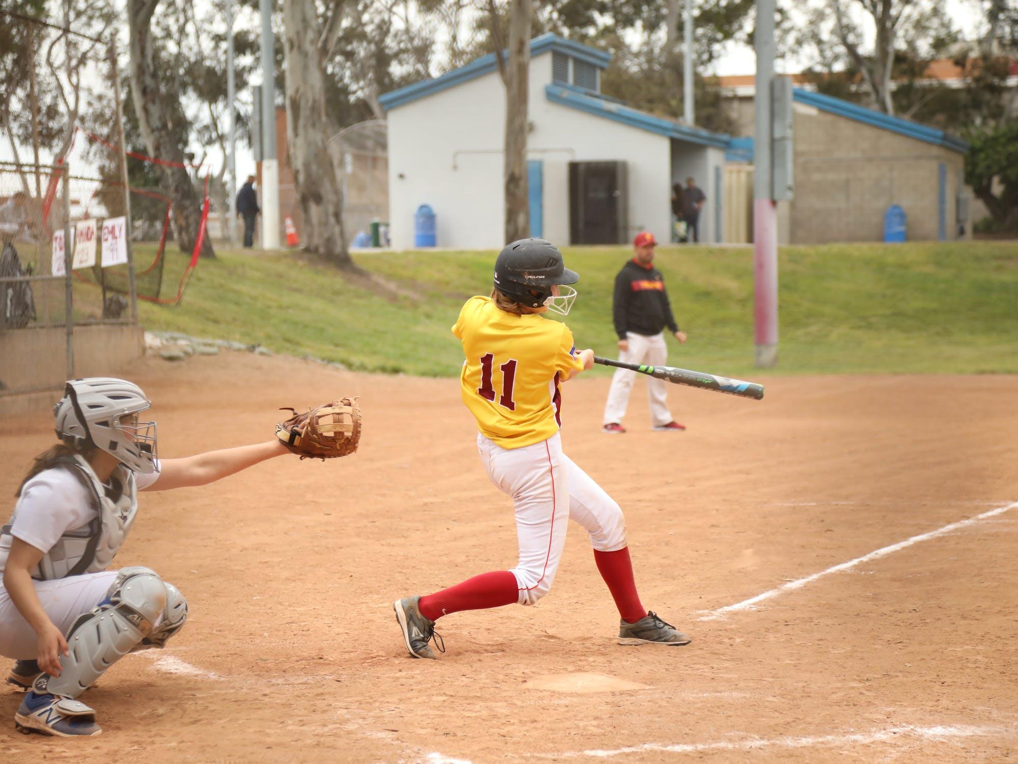 Softball player swinging bat