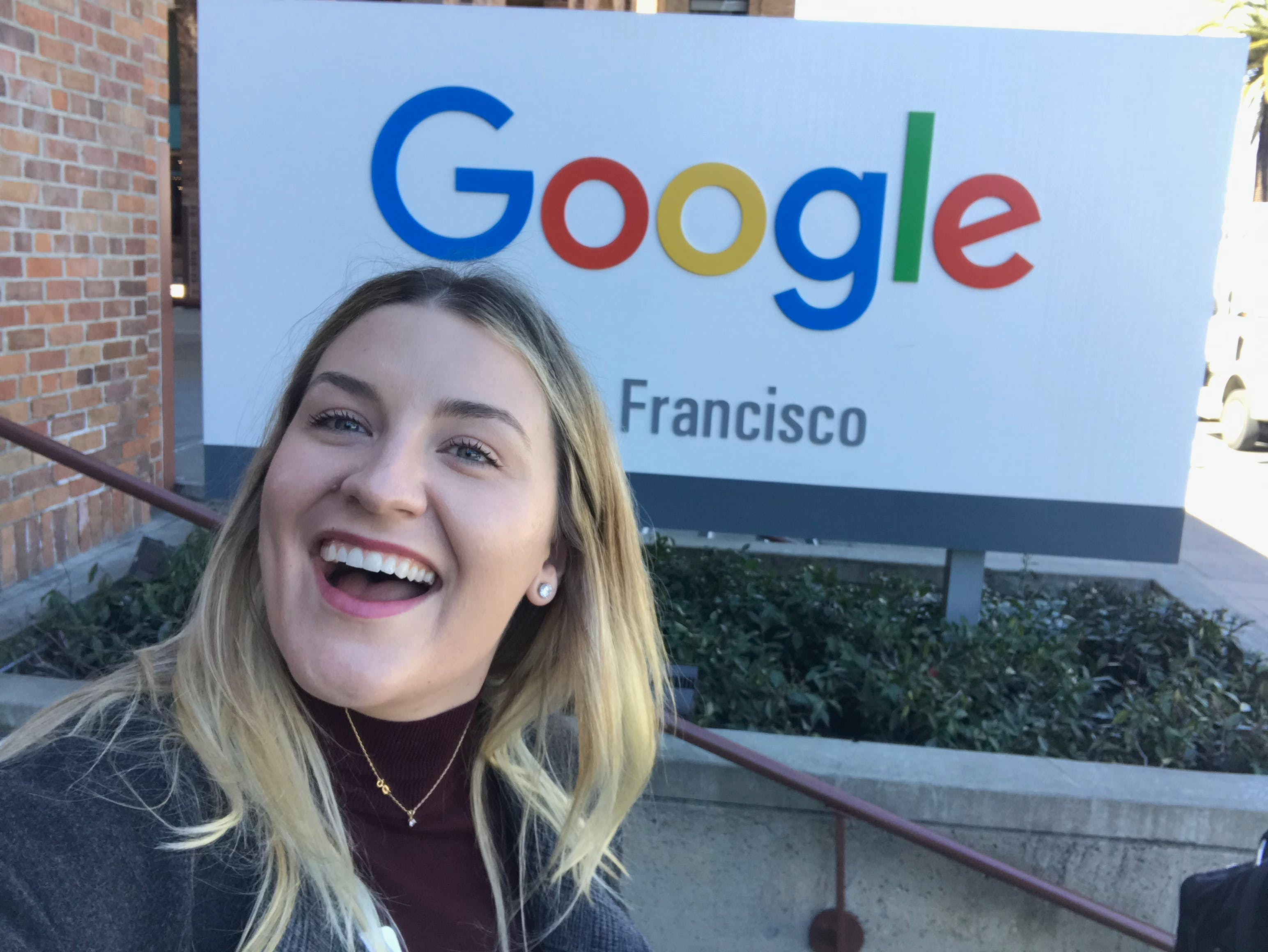 A graduate smiling in front of the San Fransisco Google office