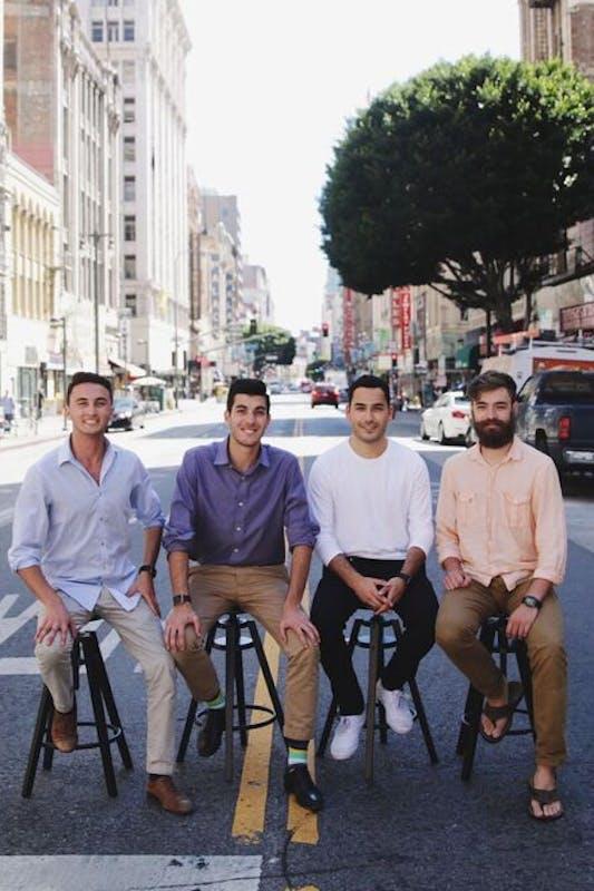 Four males sitting on stools on urban street