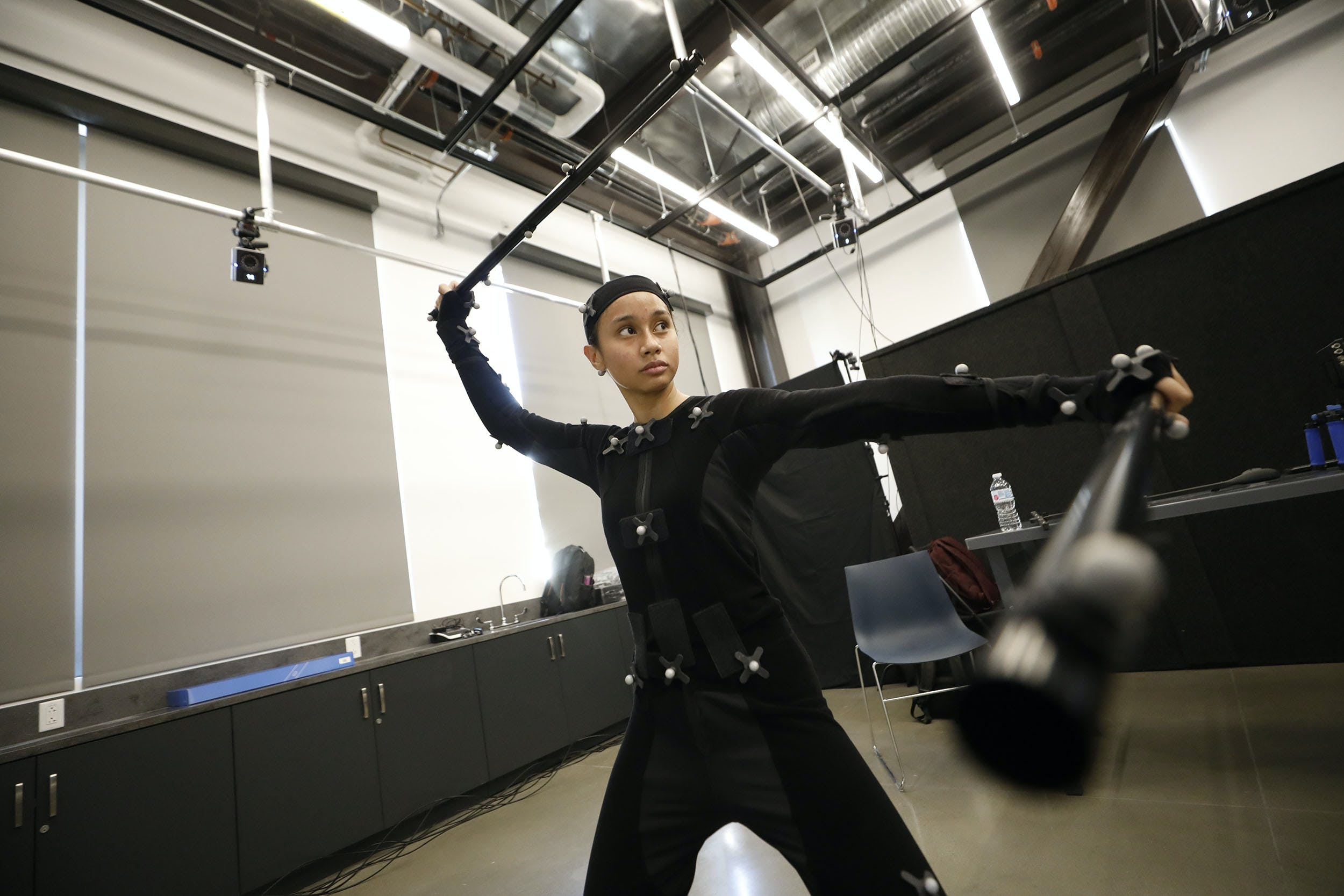 Female wearing black body suit holding to long rods for motion capture