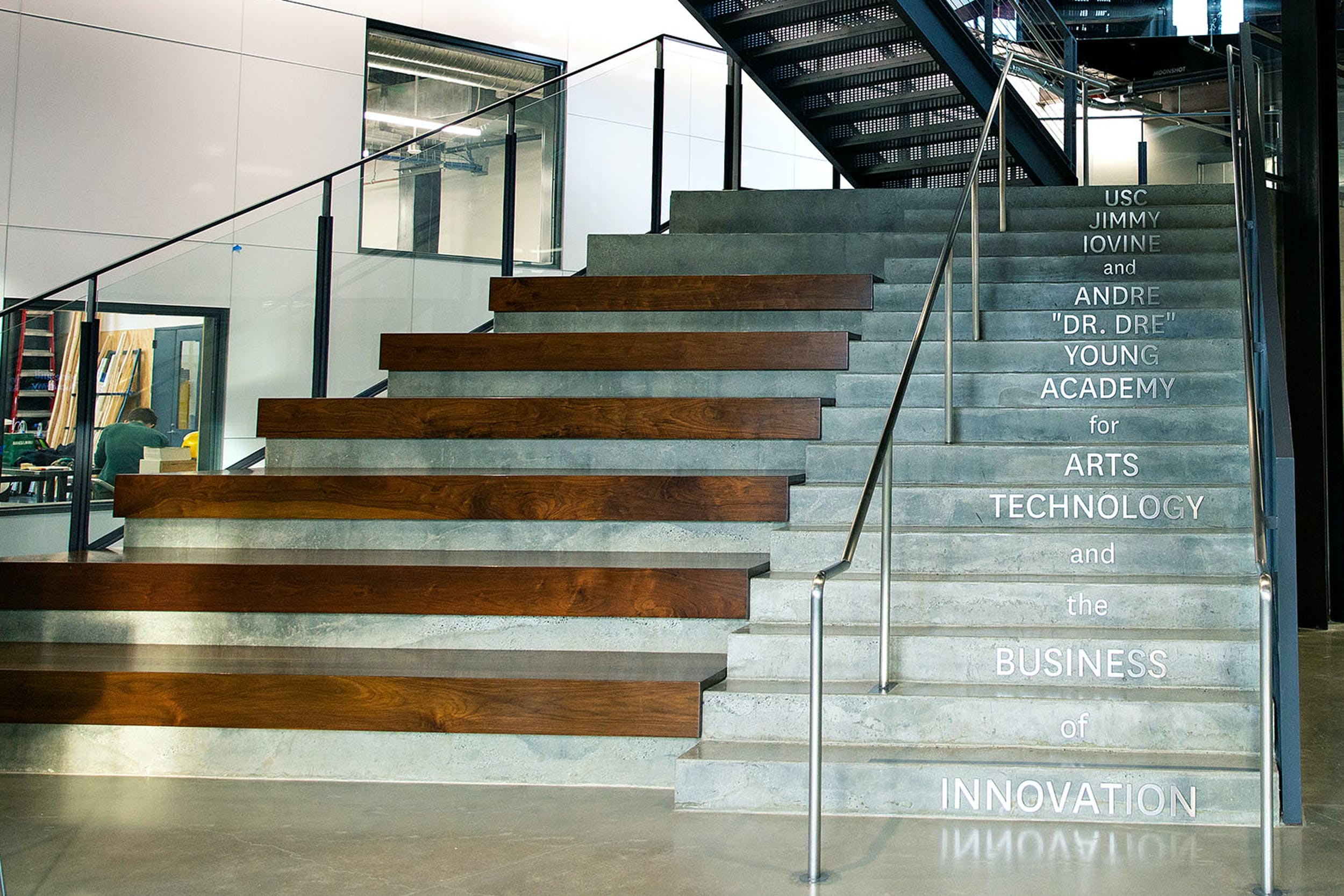 The central grand staircase made of wood, cement with steel words spelling out school name on each stair