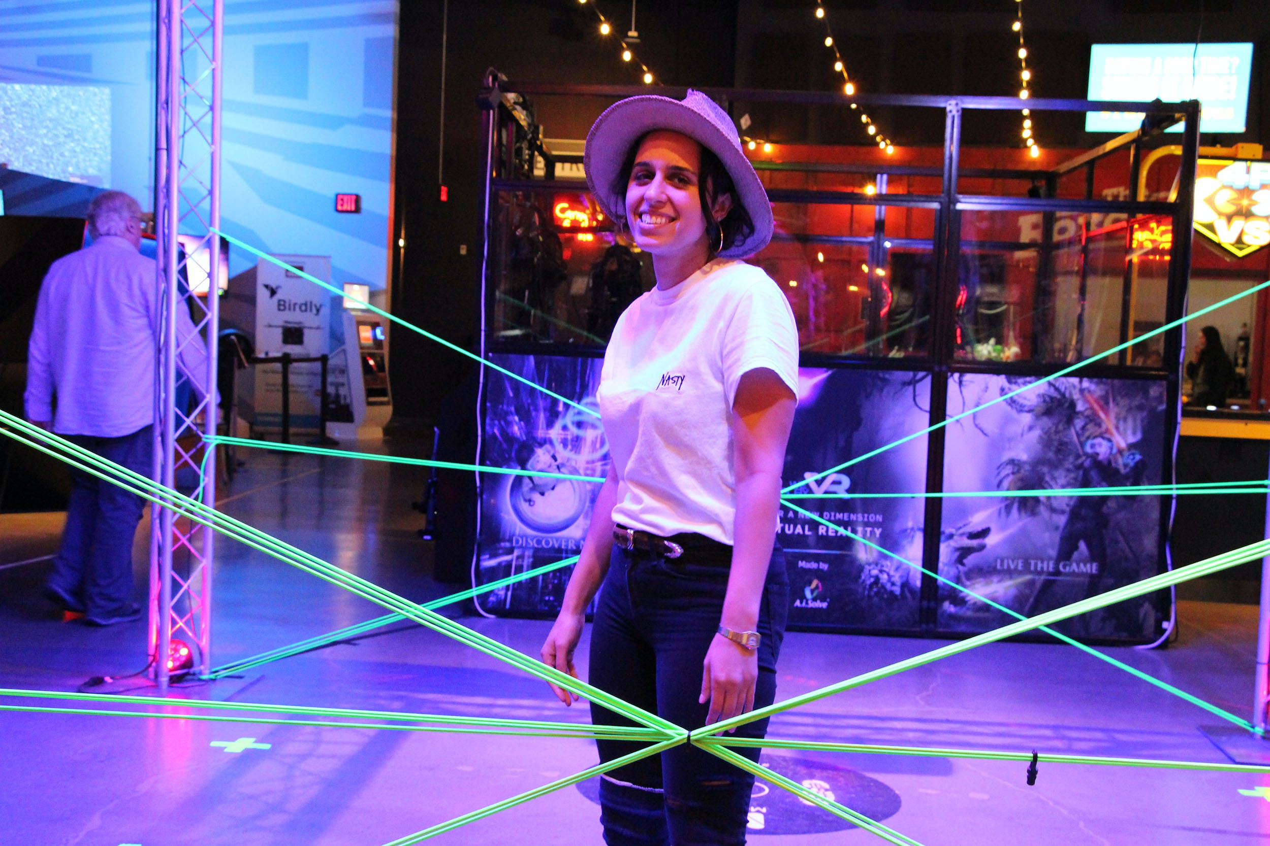 A woman stands in a neon-lighted display