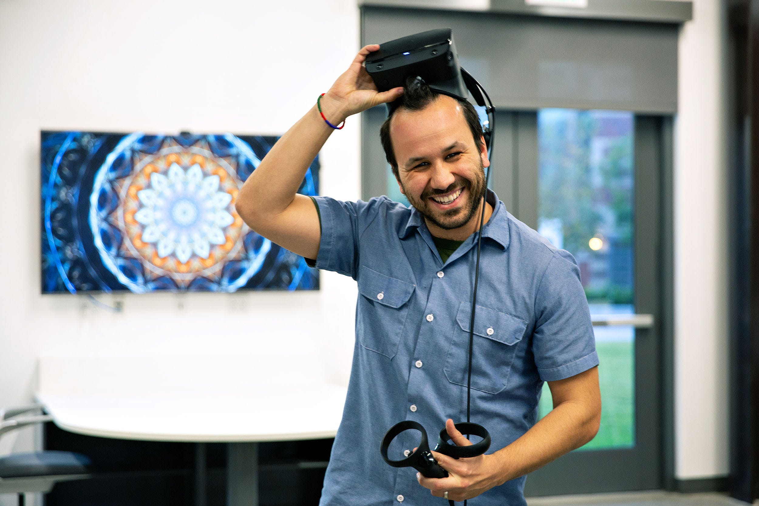 Smiling male taking off VR goggles