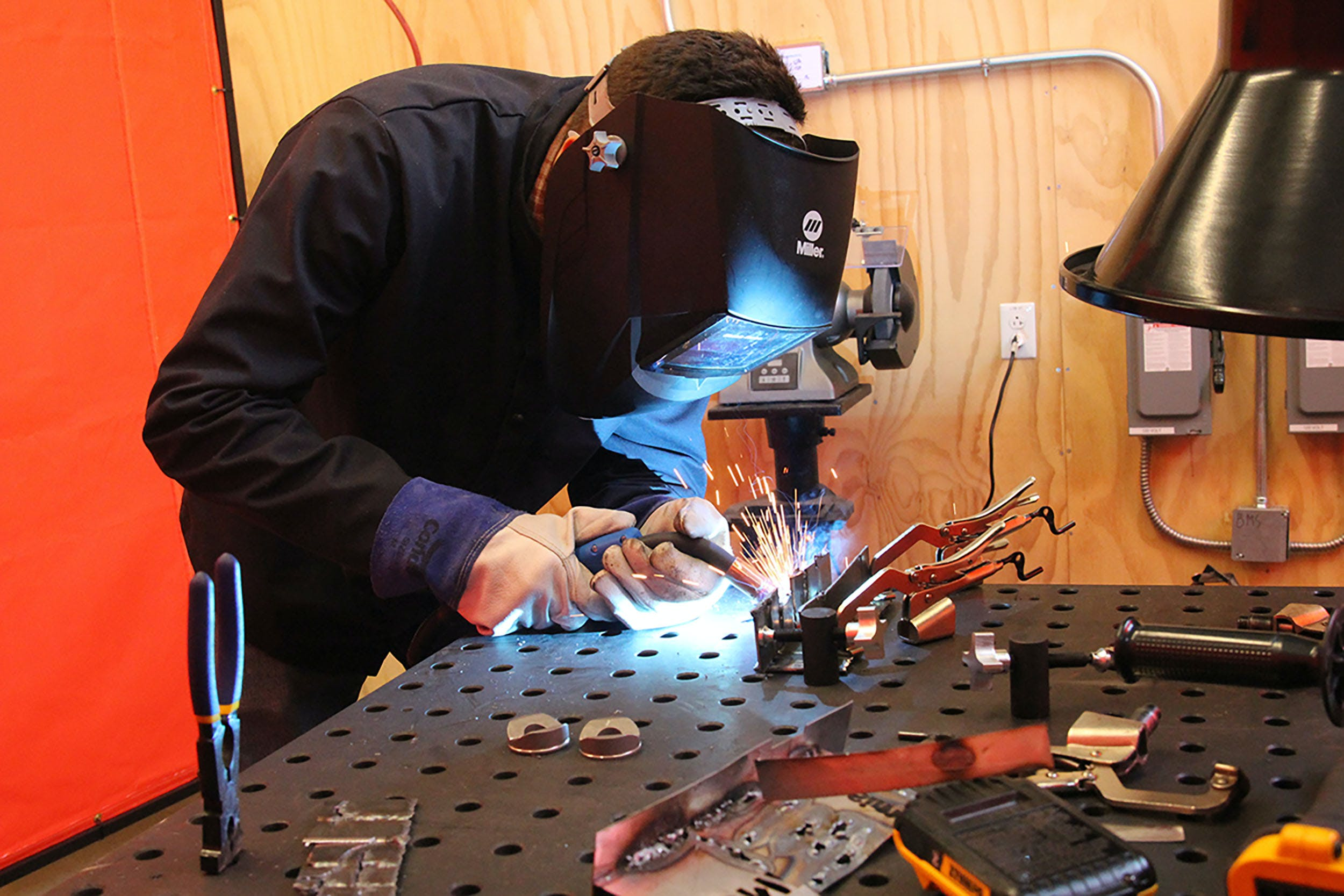 Person with welding mask welding metal