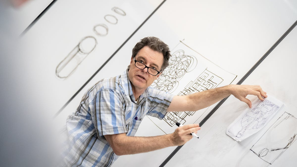 Professor instructing in front of white board