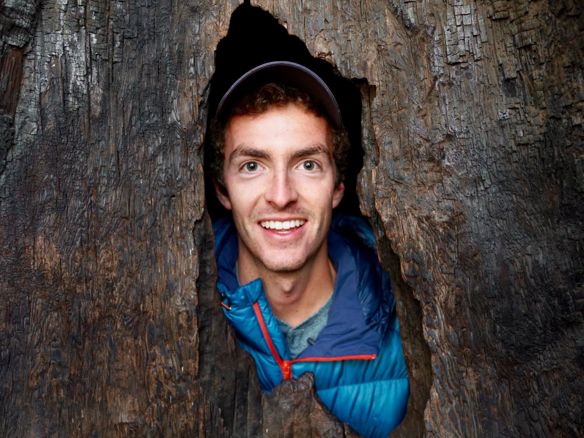 Smiling male peering through tree trunk