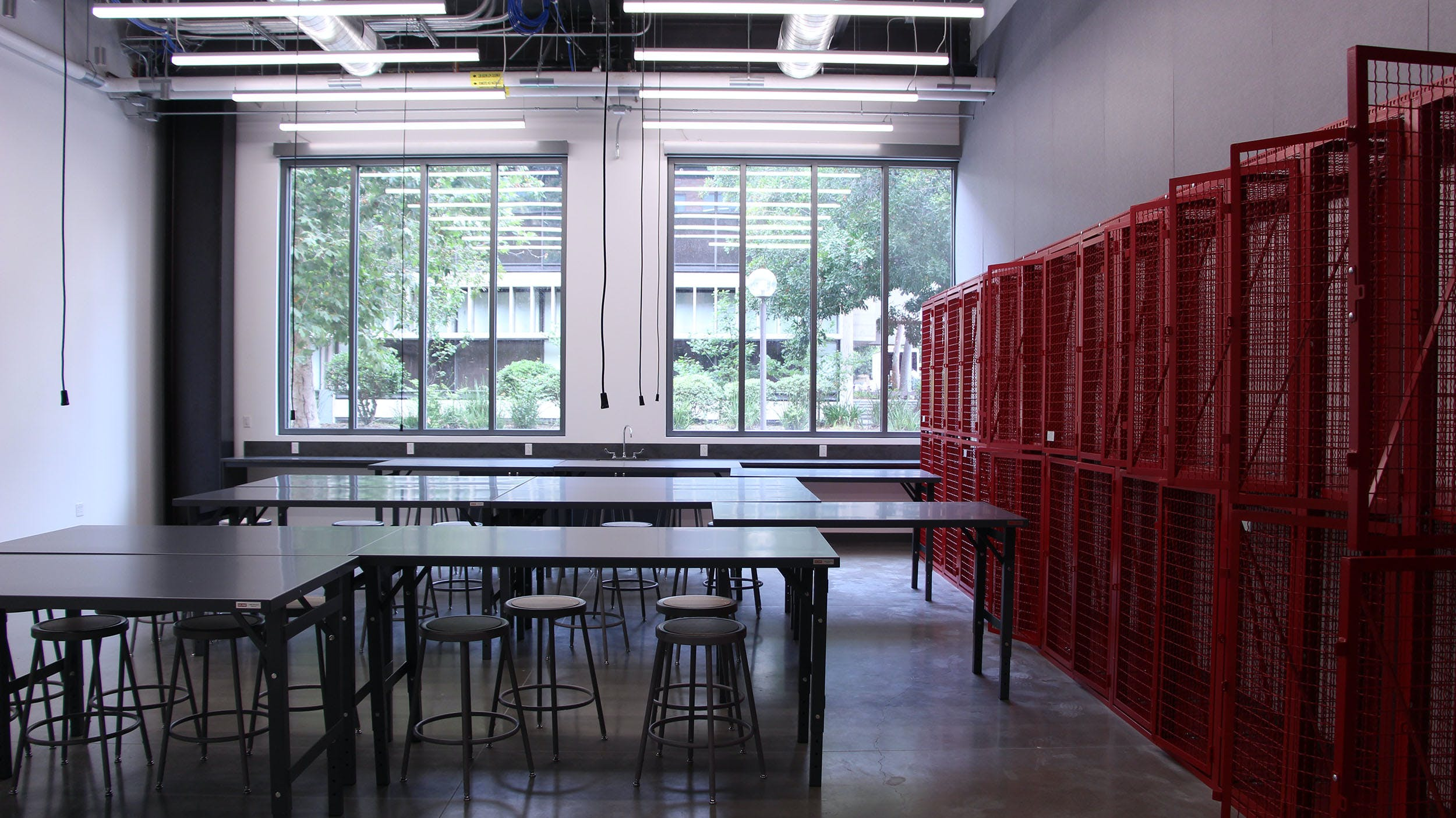 An empty classroom with long desks and red cage lockers