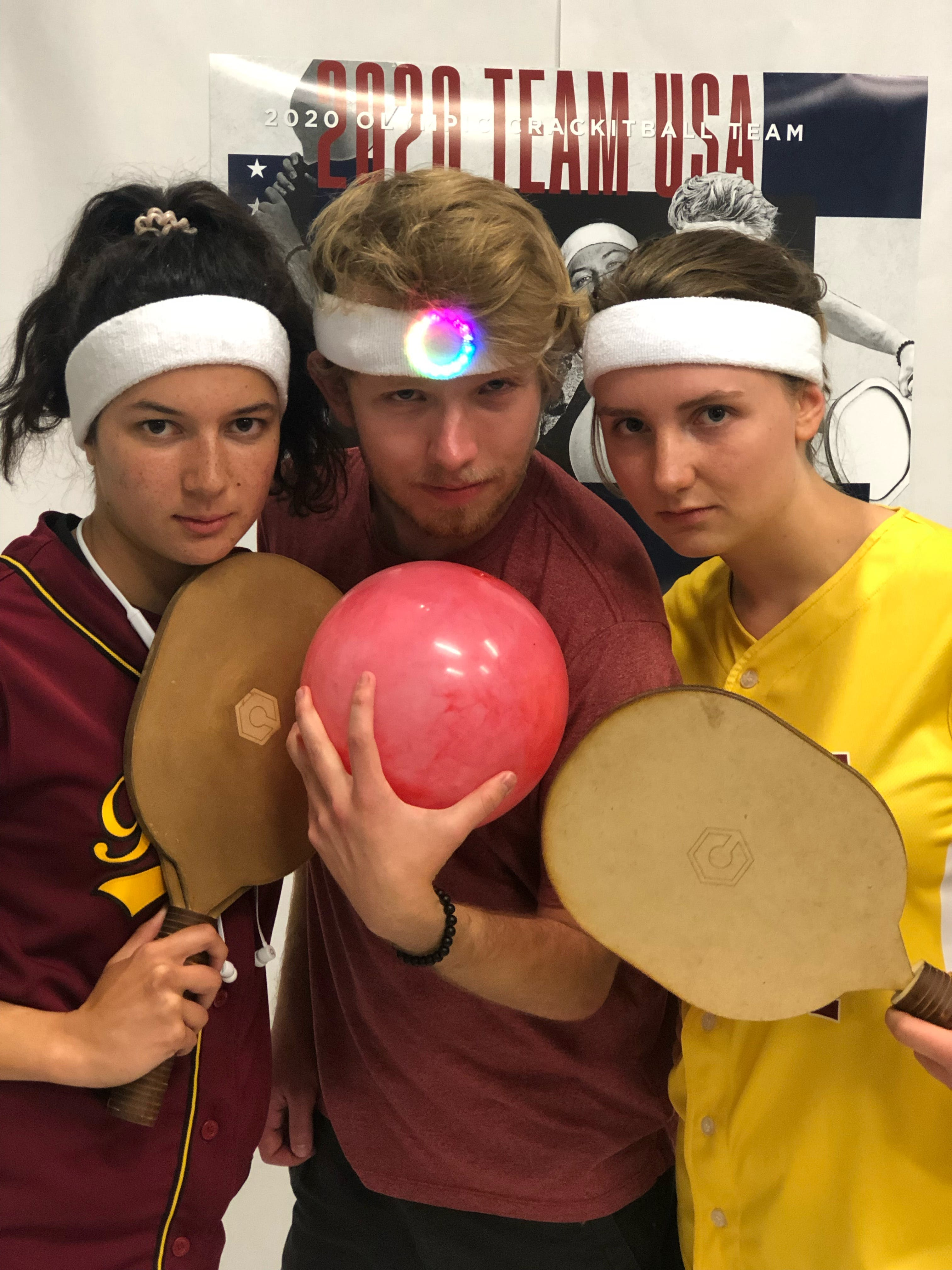 3 college students wearing white headbands staring intensely at the camera