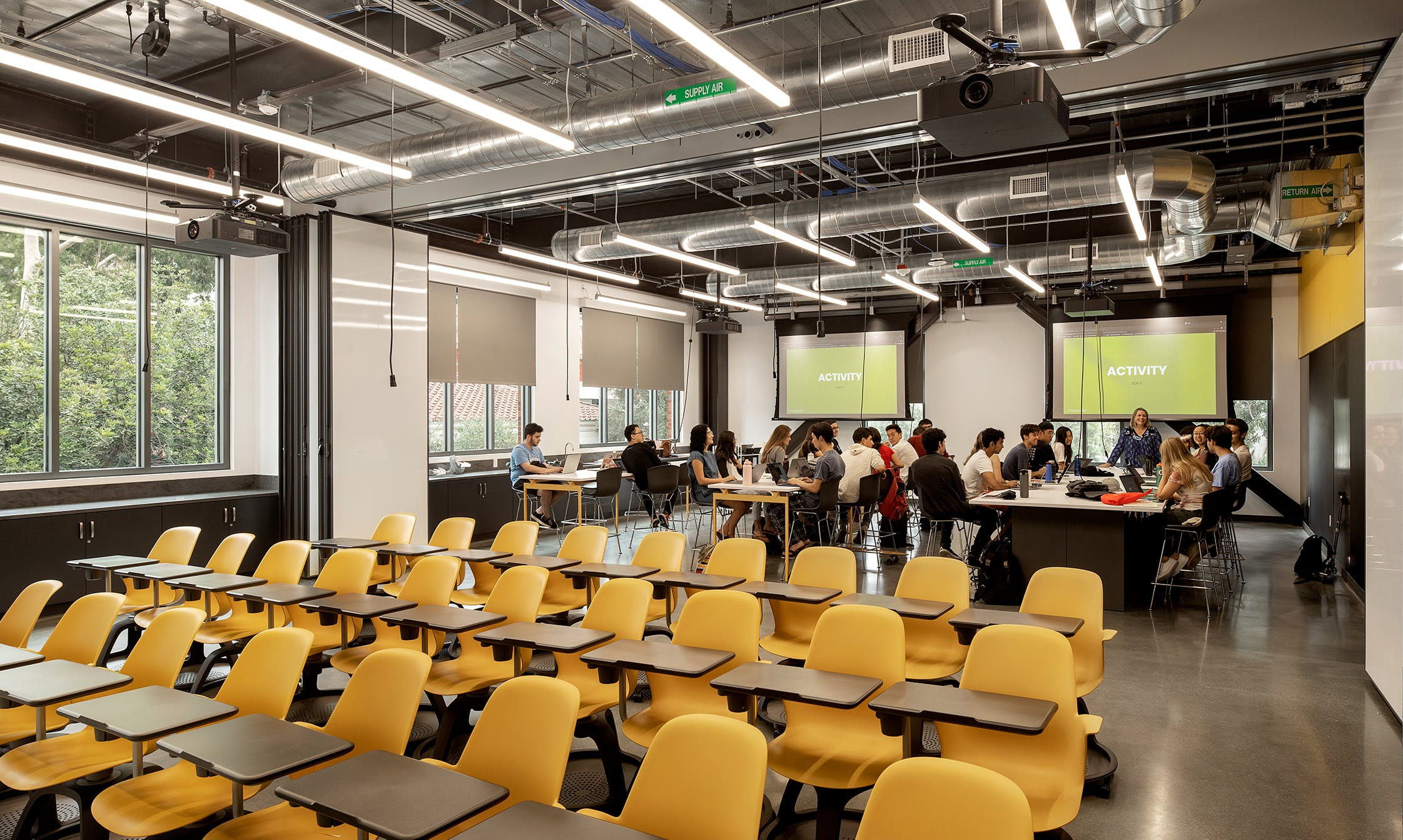 Open space classroom with empty chairs and group of students working in the background