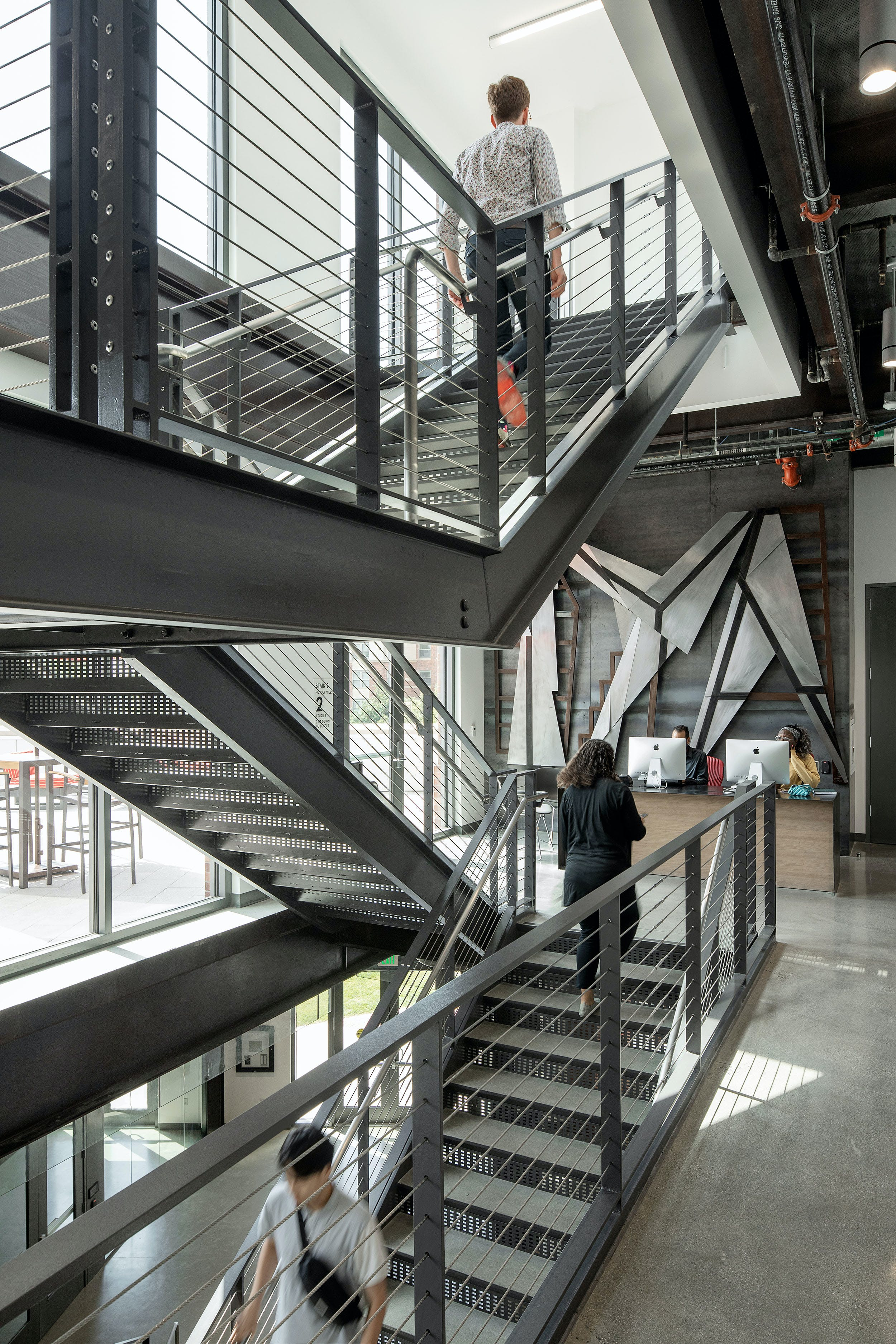 2 flights of steel staircase with people walking up