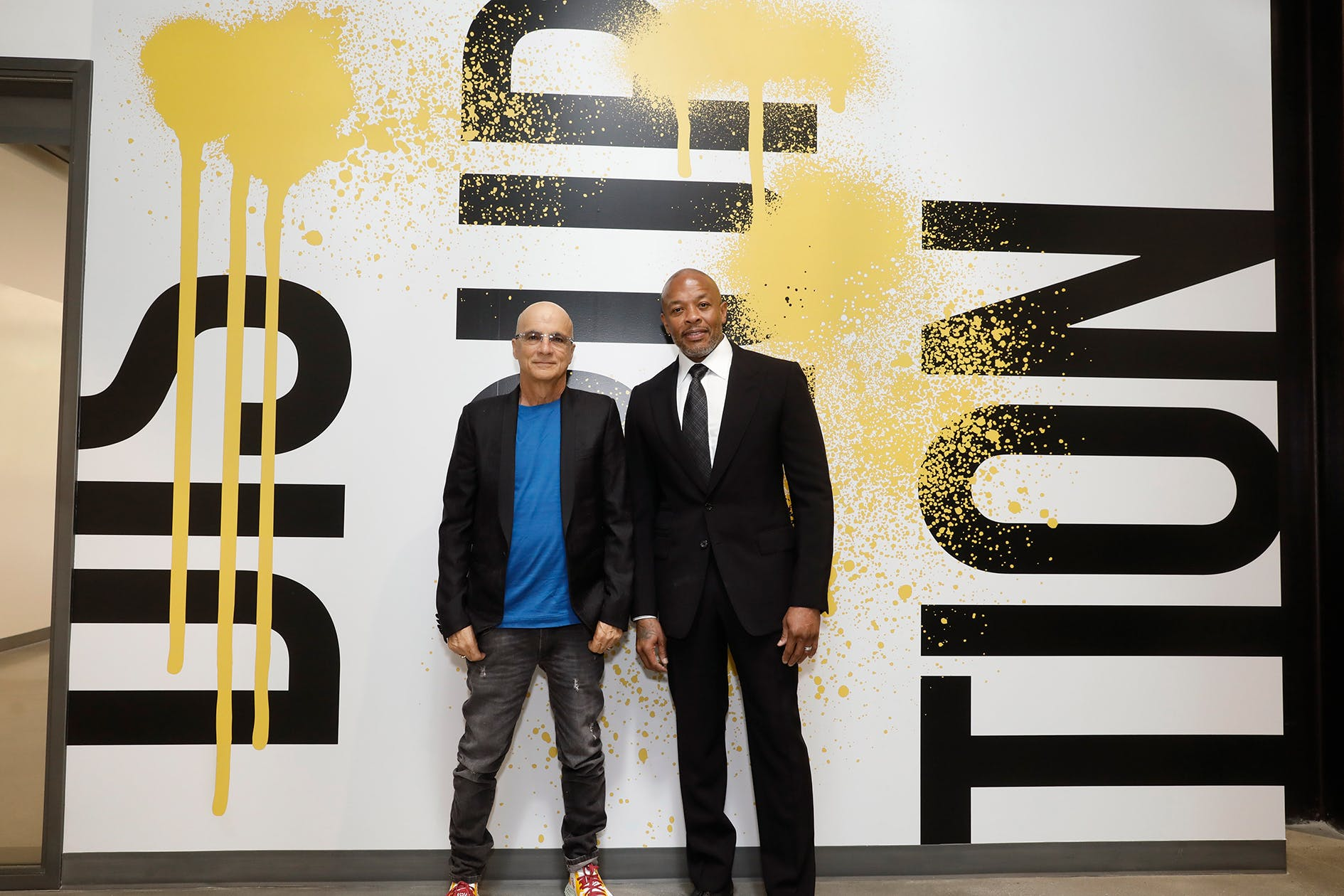 Two men standing in front of paint splattered wall