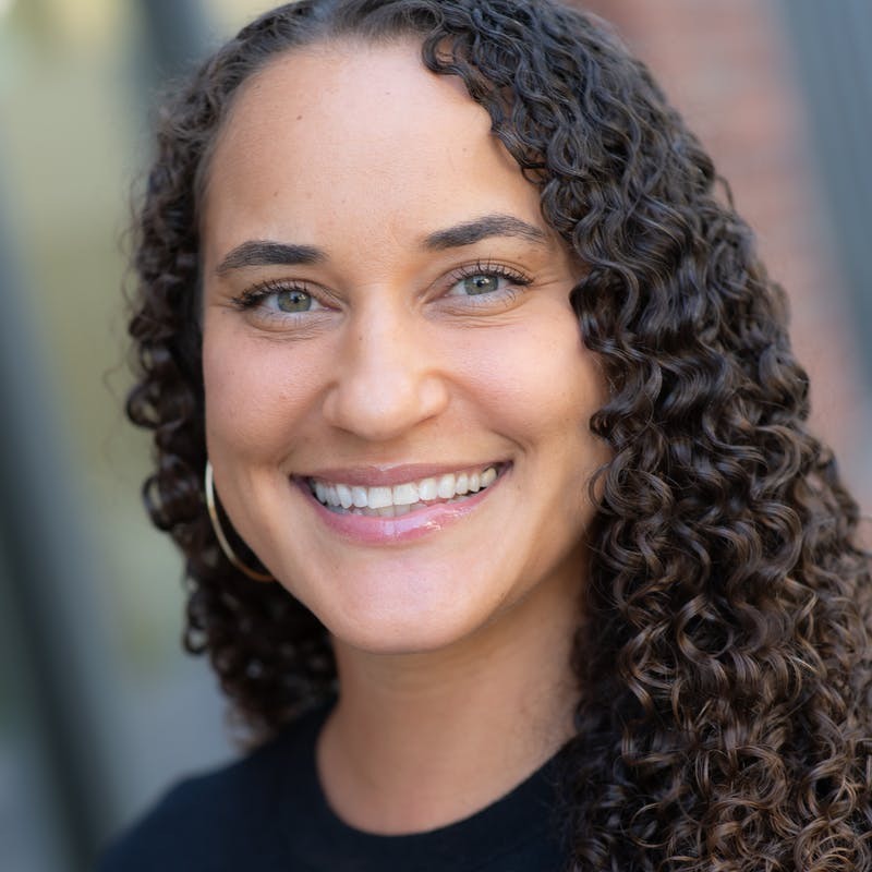 Headshot of a smiling woman with curly hair