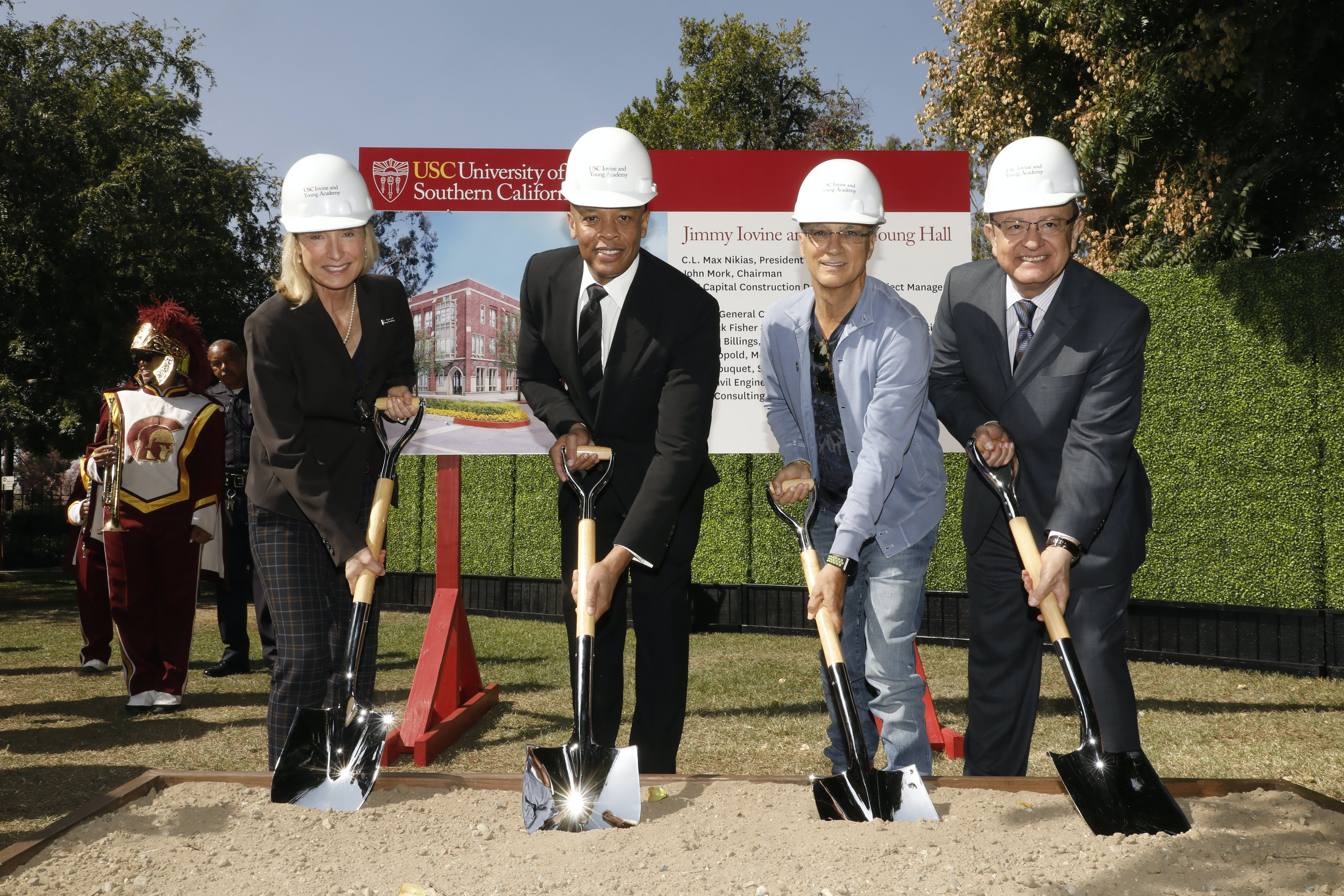 3 males and 1 female wearing white hard hats and holding shovels ready to break ground