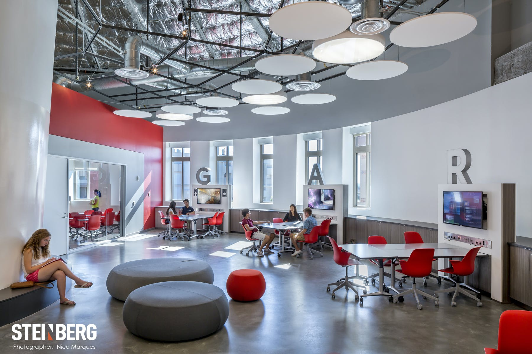 An open-space classroom with red chairs, circular grey ottomans and circular ceiling lights