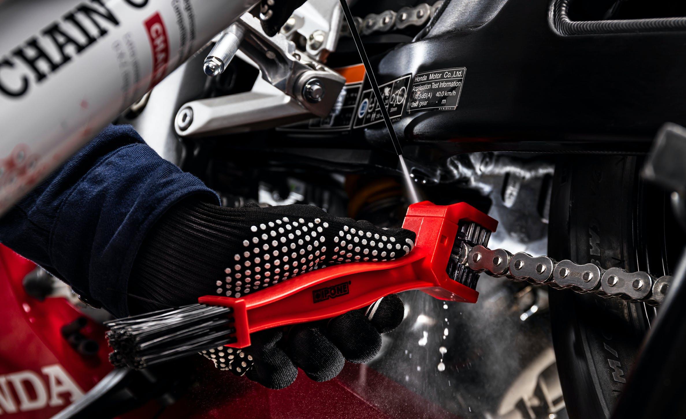 Nettoyage d'une chaîne de moto avec une brosse de chaîne