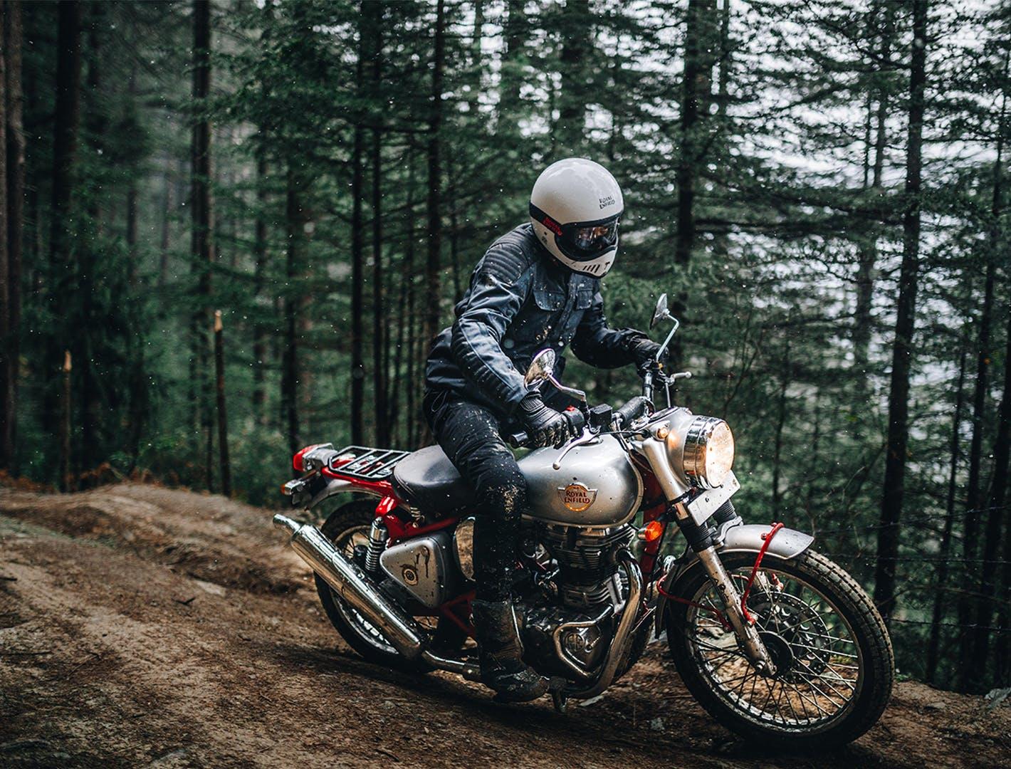 Moto 4 temps Royal Enfield Bullet Trial 350 sur un chemin de terre dans la forêt