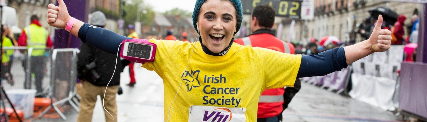 Lady finishing marathon in yellow Irish Cancer Society t-shirt