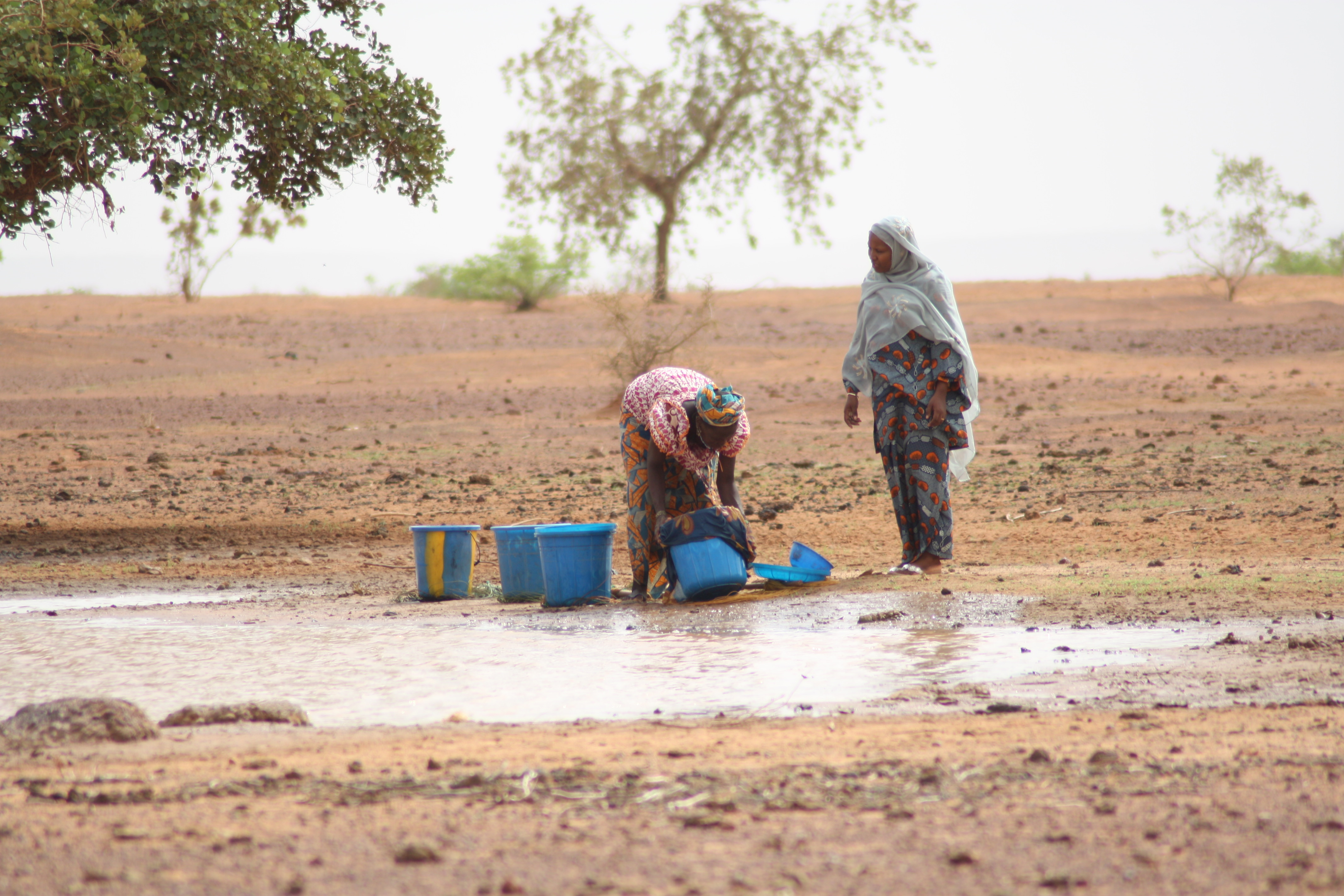 Two women collecting water from a water hole.