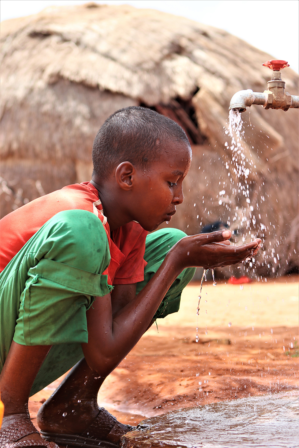 A boy drinking water with his hands.