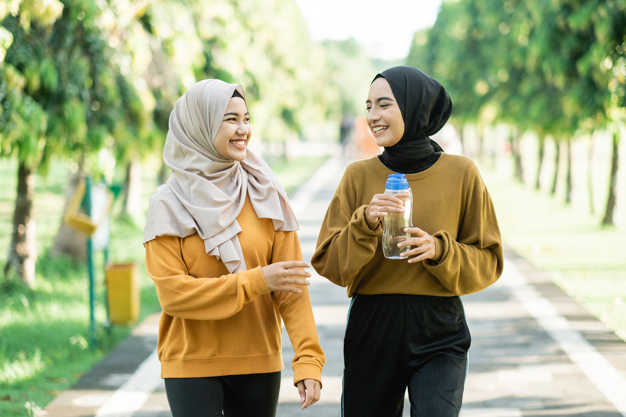 Photo of two young woman chatting to each other outside whilst walking towards the camera