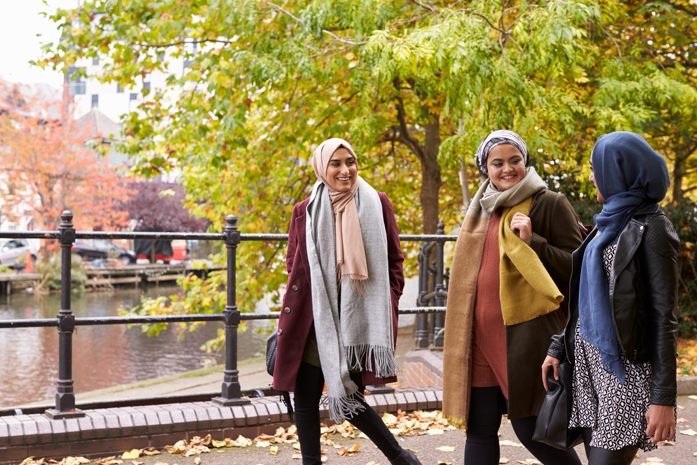 Image of three women walking and chatting to each other outside