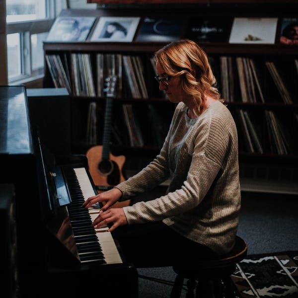 A woman plays the piano in her music room surrounded by records and musical instruments