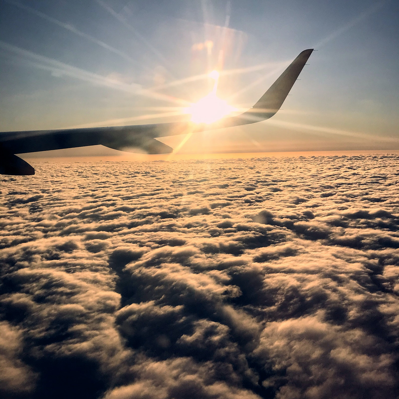 The wing of a plane above the clouds
