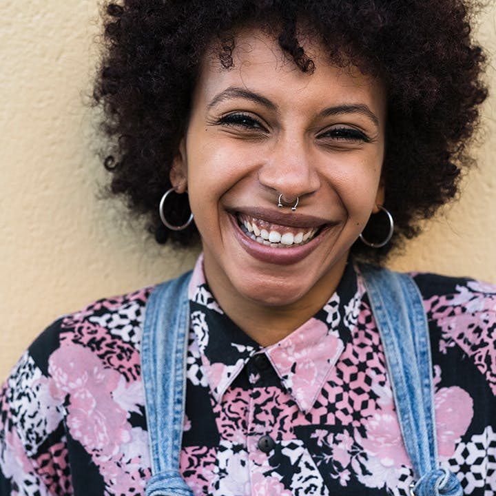 Image of a person in a patterned shirt smiling.