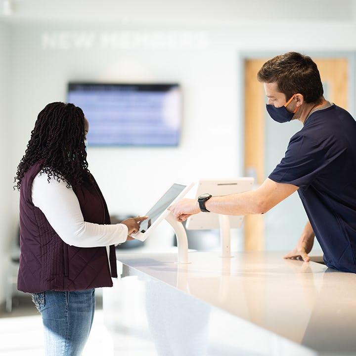 Parachute employee guiding a donor through the checkin process at a center.