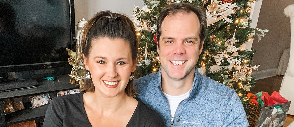 Image of man and woman smiling in front of a Christmas tree