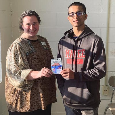 Poojan Patel, a junior at Magee High School, receives an award from Hannah Mason, Jumpstart Test Prep's Operations and Media Coordinator, for achieving a first-attempt score of 20 or higher on the English sub-section of the ACT.