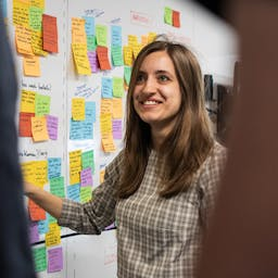 A talent standing in front of a wall with sticky notes