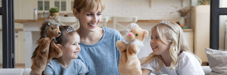 Junge Mutter mit ihren zwei Töchtern beim spielen mit einem Puppentheater