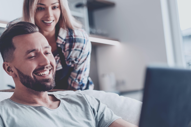 Paar guckt freudestrahlend auf einen Laptop Bildschirm