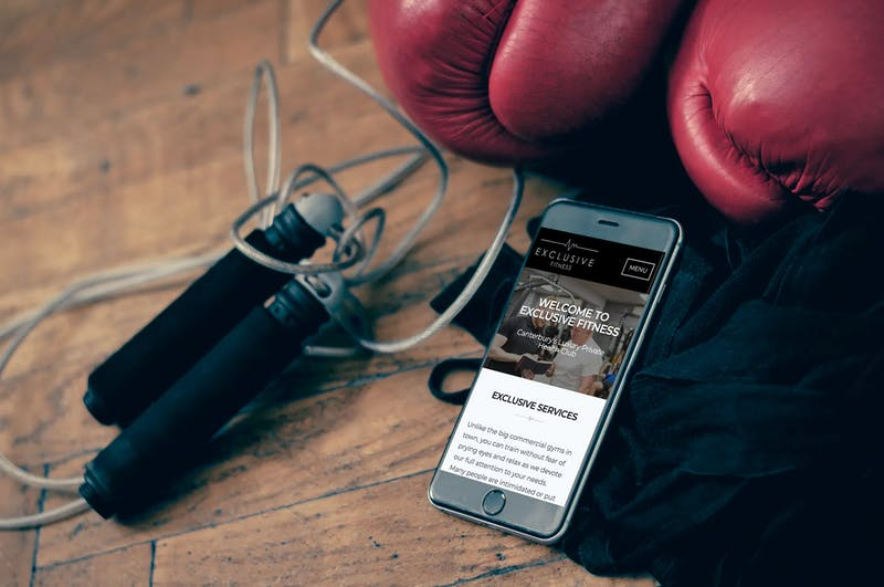 Exclusive Fitness website on iPhone 8 surrounded by gym equipment