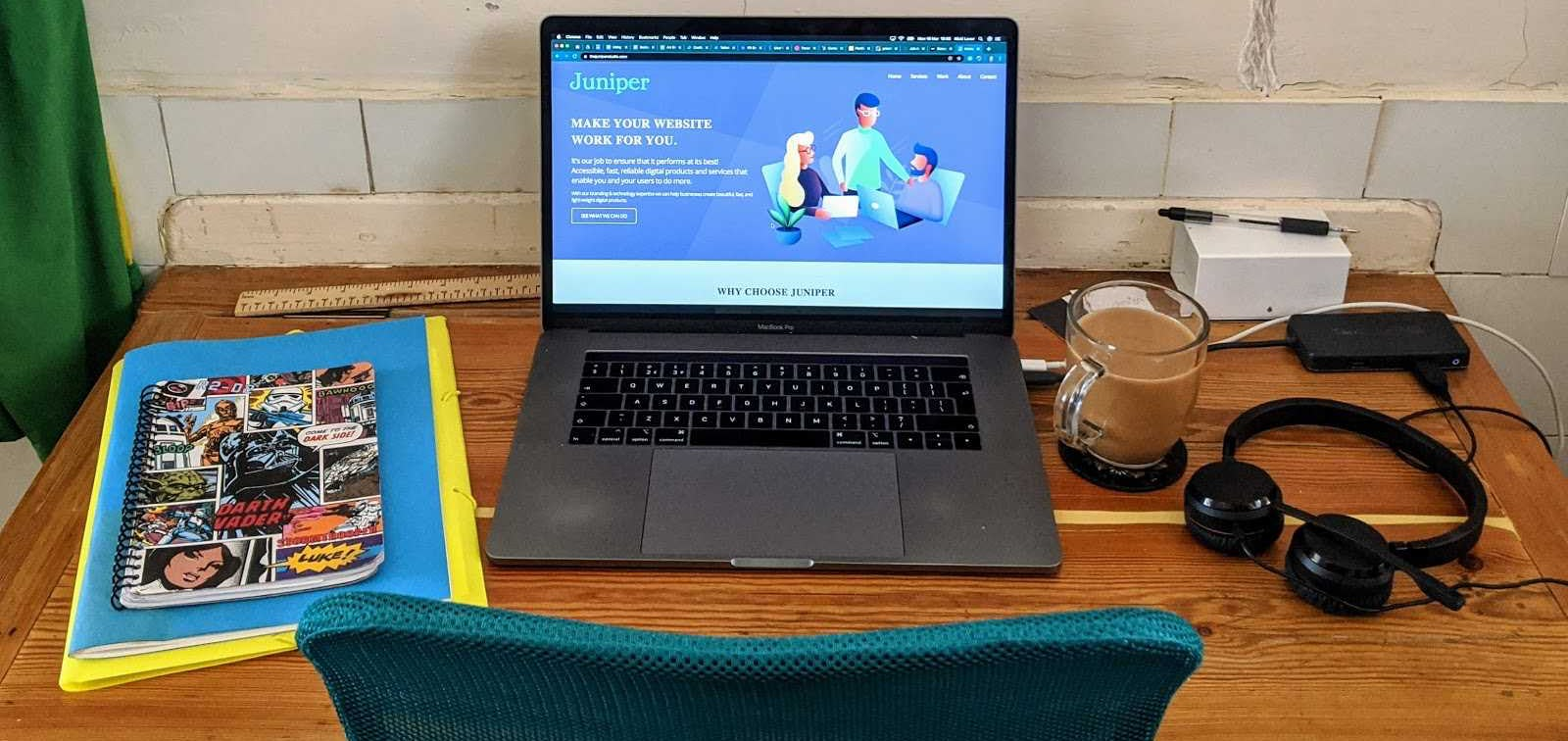 Photo of desk with laptop, coffee and headphones