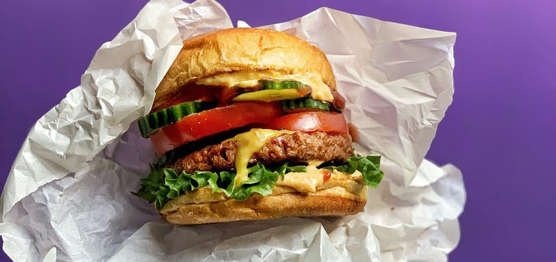 A hang holding a large Cheeseburger