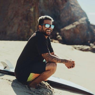 Man wearing Oakley sunglasses with surfboard