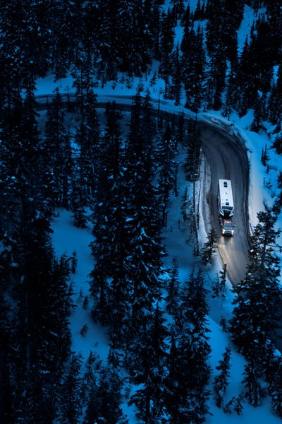 Aerial shot of winding mountain road at night with snow covered pine trees and a Keystone Fuzion toy hauler being pulled by a GMC Sierra HD Denali.